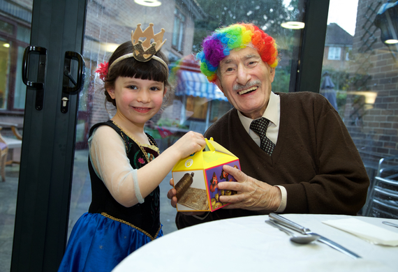Sadie saklow from brondesbury park shul cheder visiting jewish care's clore manor celebrating purim with resident philip sonenfeld listing